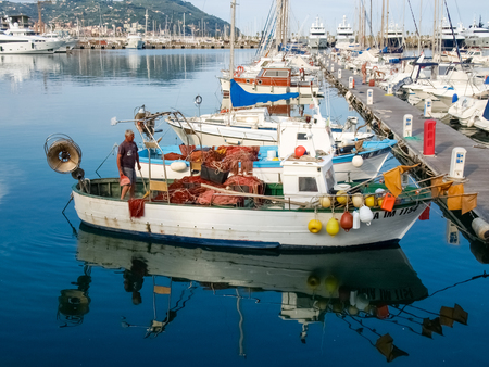 Oneglia, Italy - June 9, 2015: Fisherman system networks on the small boat moored in the harbor Publikacyjne