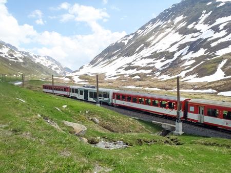 Andermatt, Switzerland - June 4, 2015: Matterhorn Gotthard train through the valley that leads up to the Oberalp pass. Publikacyjne