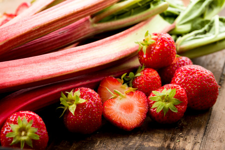 rhubarb: Fresh rhubarb and strawberries on a wooden underground Stock Photo