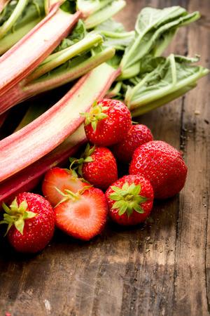 Fresh rhubarb and strawberries on a wooden underground Standard-Bild