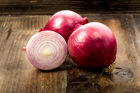 Red onions on a wooden background Stock Photo