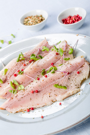 brook trout: smoked trout fillet with pink pepper and fresh cress Stock Photo