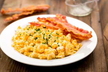 Freshly fried bacon served with scrambled eggs and chives Stockfoto
