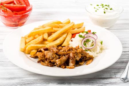 carnes y verduras: Plato Kebab con patatas frescas ensalada de repollo y cebollas fritas