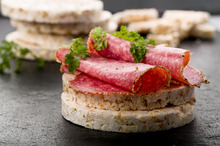spelled: rice wafers topped with salami and fresh herbs