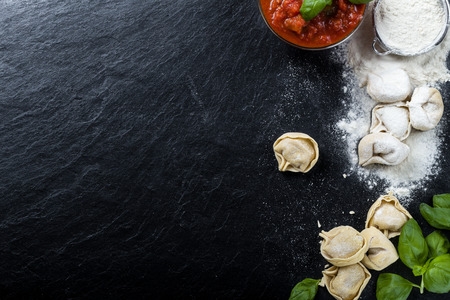 Freshly prepared Tortellini on a slate, with ingredients photo