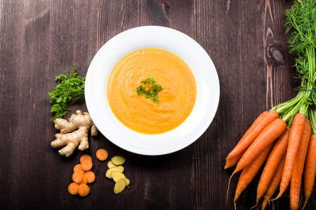 Fresh carrot ginger soup with ingredients on background