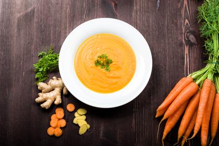 jengibre: Zanahoria sopa de jengibre fresco con ingredientes en el fondo