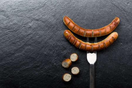 Salchicha frita en un tenedor clavado en un fondo