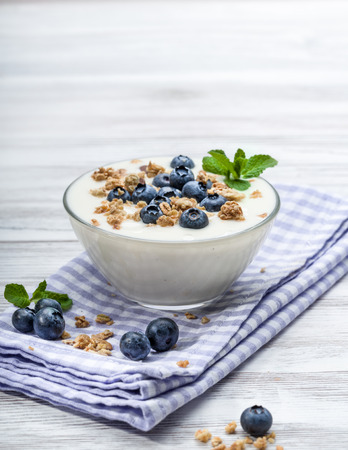 quark: Fresh blueberry yogurt with granola and mint on a background