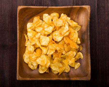 nibble: Potato chips with herbs in a wooden bowl