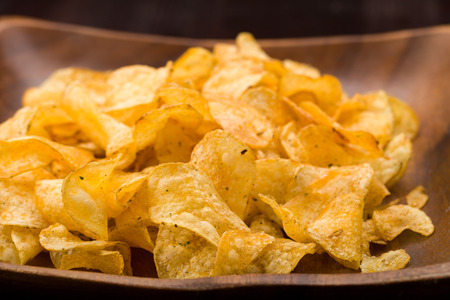 nibbles: Potato chips with herbs in a wooden bowl