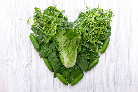 Green vegetables in heart shape on a background