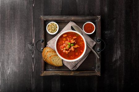 solyanka: Fresh solyanka on a tray on a wooden background