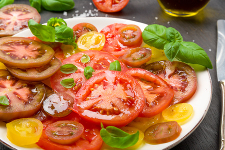 Colorful tomato salad with basil on a subsurface Stock Photo