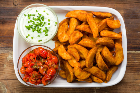Potato wedges with dip and roasted tomatoes and fresh chives Stockfoto