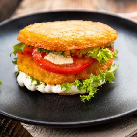 papas doradas: tortitas de patata con queso tomate y lechuga en un plato