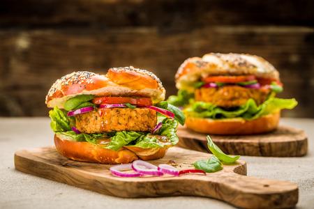 Healthy vegan burger with fresh vegetables and chili sauce Standard-Bild