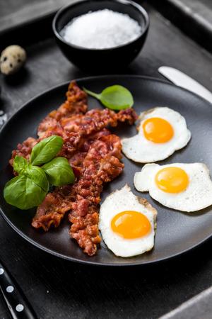 huevos de codorniz: Tocino y huevos de codorniz con albahaca Foto de archivo