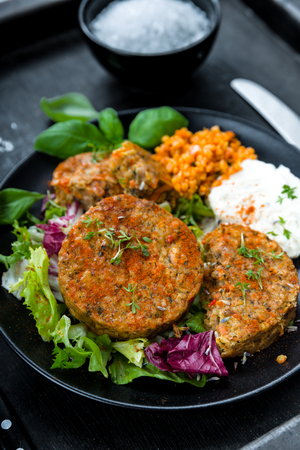 Patties on lettuce with bulgur and fresh herbs