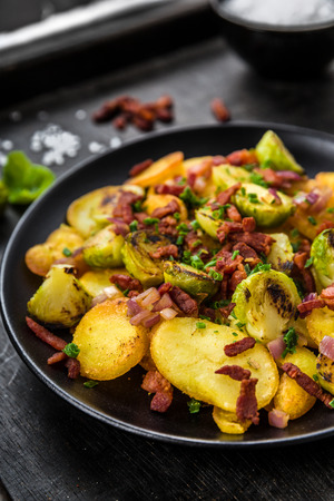 brussels sprouts: Fried potatoes with Brussels sprouts and bacon on a plate
