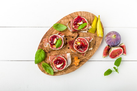 cowardly: Bruschetta with figs, basil, cranberry and ham Stock Photo