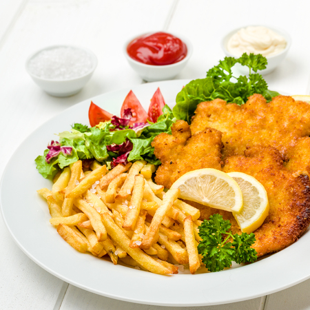Chicken cutlets with french fries, ketchup, mayo, lemon and salad Stockfoto