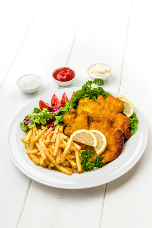 breading: Chicken cutlets with french fries, ketchup, mayo, lemon and salad Stock Photo