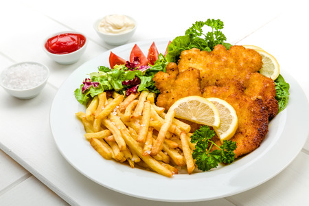 Chicken cutlets with french fries, ketchup, mayo, lemon and salad Standard-Bild
