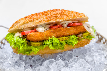 pescado frito: fried fish on a bun with lettuce, tomato and cucumber