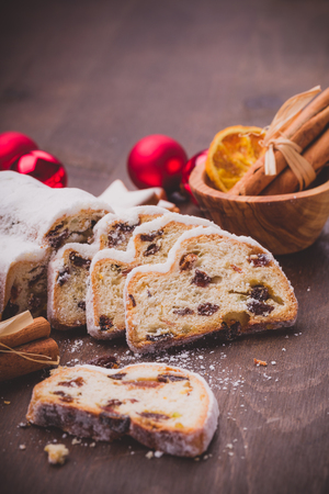 christmas baker's: Christmas stollen sliced on a wooden underground with cinnamon Stock Photo