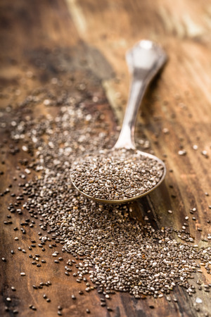 roughage: Chia seeds on a spoon on a wooden background
