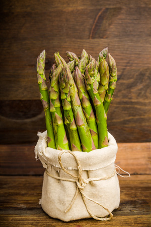 tied in: Asparagus tied in a bag on a wooden background Stock Photo
