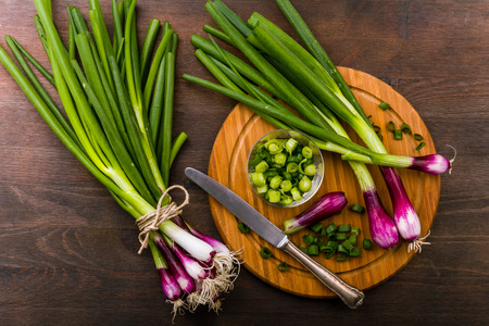 spring onions: Fresh Red spring onions scallions on a wooden underground