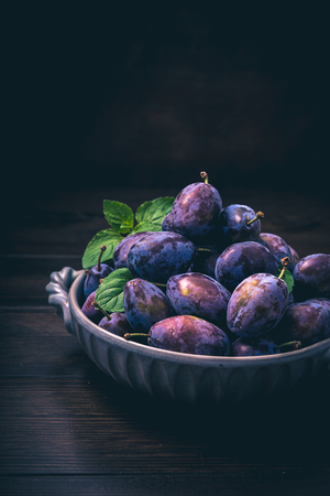 purple leaf plum: Plums in a bowl on wooden with mint