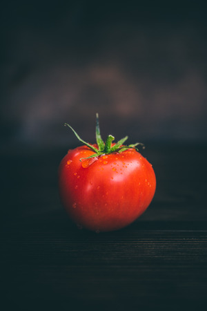 Tomato on dark wood with water drops