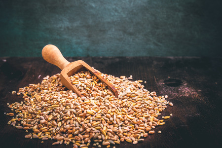 Five kinds of cereal in a heap on a wooden spoon