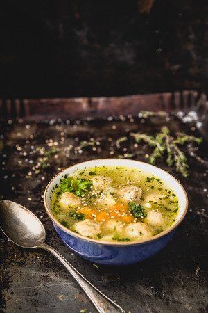 fresh meatball soup in bowl on dark background, dark background
