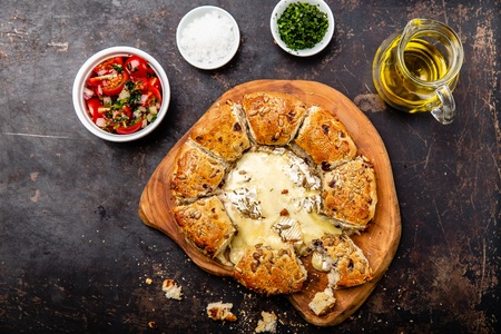 Camembert baked in the oven with herb bread served with tomato salad and olive oil