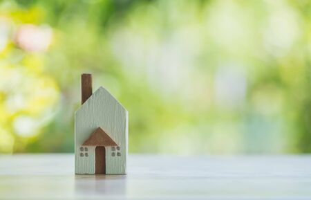 Closeup miniature house with green nature background on wooden table with copy space concept. Stok Fotoğraf