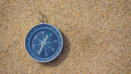 Navigational Compass On Sandy Beach with copy space.