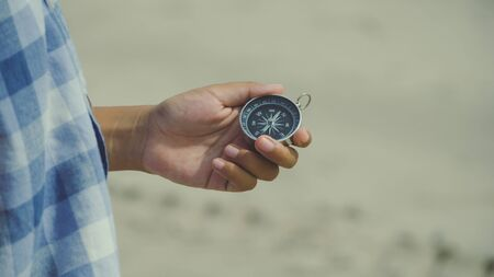 Asia boy holding compass on the beach. Use compass for navigate to adventure.