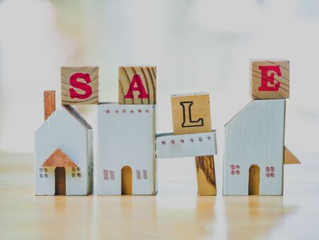 Sale word written cube with wood home on table. Concept for loan, property ladder, financial, mortgage, real estate investment, taxes and bonus. Stok Fotoğraf