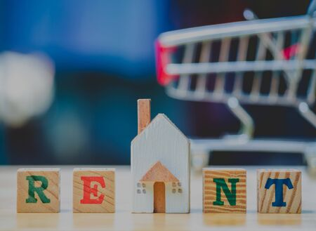 RENT word written cube in front off shopping cart  home on wooden background. Concept for loan, property ladder, financial, mortgage, real estate investment, taxes and bonus.