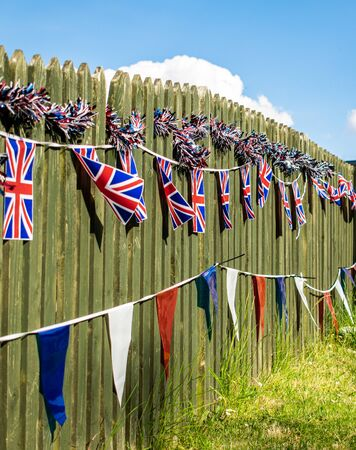 Union Jack bunting on a fence row, many flags in row on a string, front of garden VE day decorations in UK, memorial symbol of winning second world war, Banque d'images - 147122279