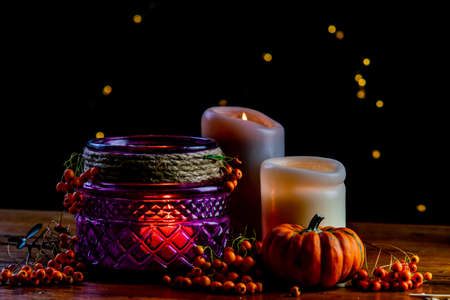 Purple lantern, orange golden nugget pumpkin rowan berries and two candles on wooden rustic table and black background with yellow bokeh dots, autumnal warm mood in cozy home.
