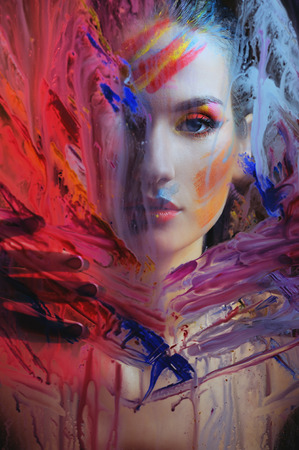 portrait of beautiful woman in color paint splash behind the painted color glass photo