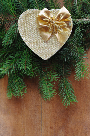 Golden gift box with christmas presents and branch of xmas tree on wooden background photo