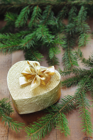 Golden gift box with christmas presents and brunch of xmas tree on wooden background photo