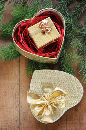 Christmas tree and golden gift box with xmas presents on texture wooden background photo